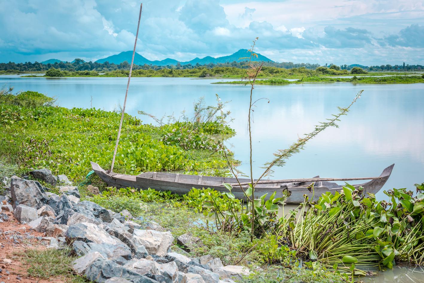 Une barque surplombe une large étendue d'eau causée par la pluie. Le paysage vert ressort.